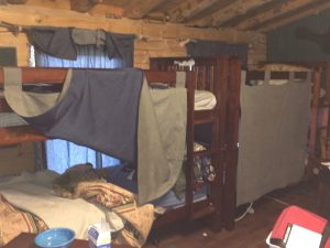 One of the bed curtains raised.  They also slide.  See the denim on the inside that acts light a light barrier.