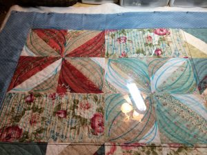 Acrylic plastic over quilt.